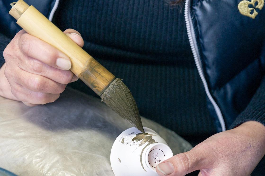 ダミ筆で呉須を器に落として広げ、余分なものは筆に吸わせて戻して描いていきます。