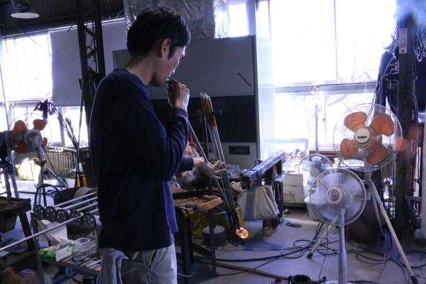(3)吹きの工程。先に少し空気を入れ形を整えてから足元の型へセットする瞬間。いよいよここから「型吹き」です。