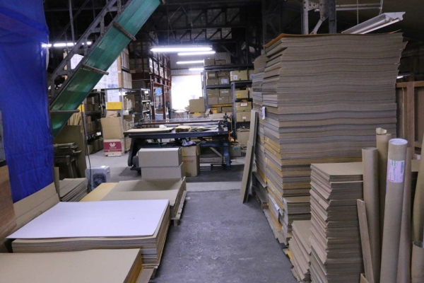 A workspace for box making: You can see cutting machines and relevant documents.