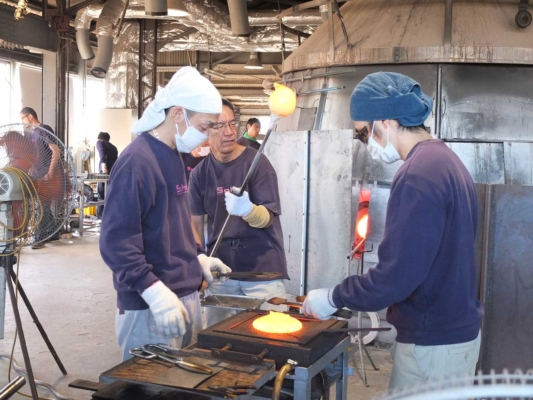 のばし:液体の硝子を板状に「のばし」てお皿を作るところ。炉から運ばれてくる硝子の塊はまるで火の玉のよう。