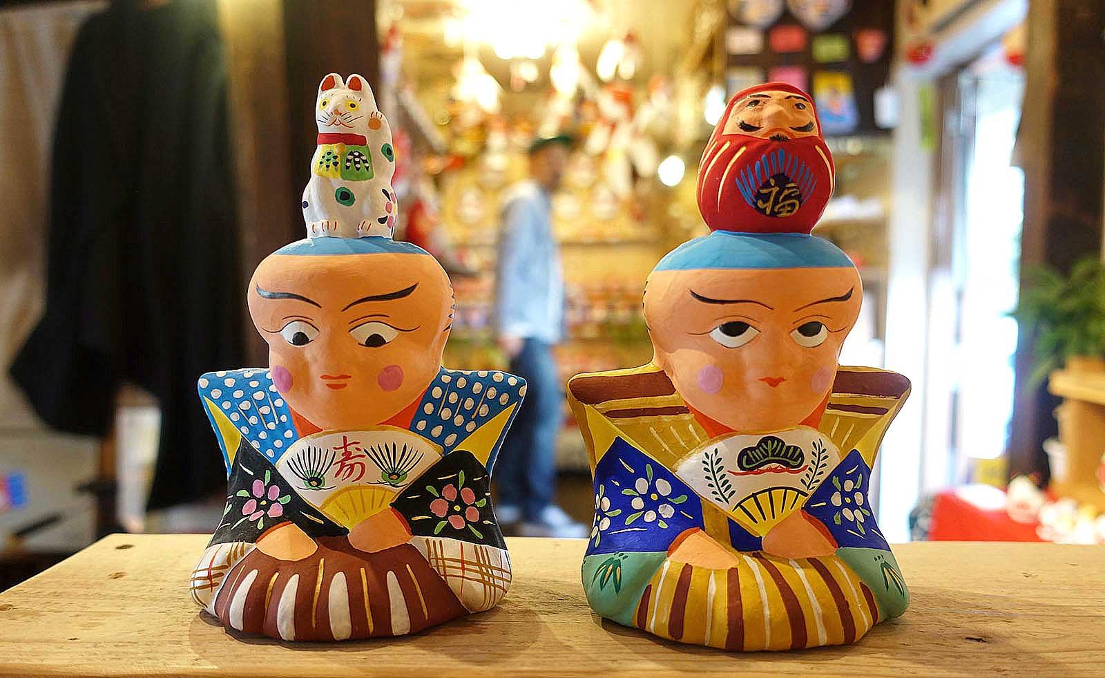 色使いが素敵な土人形。縁起もの×縁起ものという贅沢な組み合わせの「福助乗り招き猫」と「福助乗り達磨」/福島県会津若松