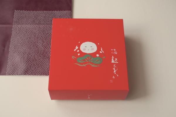 小豆色の包装紙をひらくと、真っ赤な箱が。わくわく。