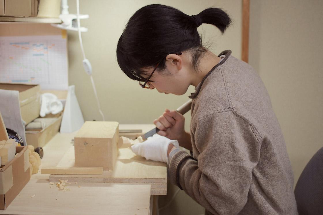 神泉さん。机に固定されたあて木を使って、彫ります