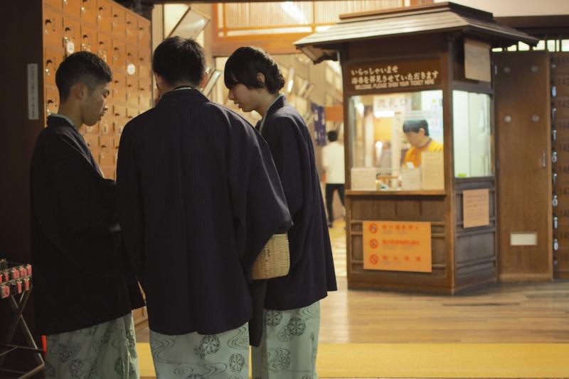 道後温泉の玄関前。若い男性陣の手に、かご。