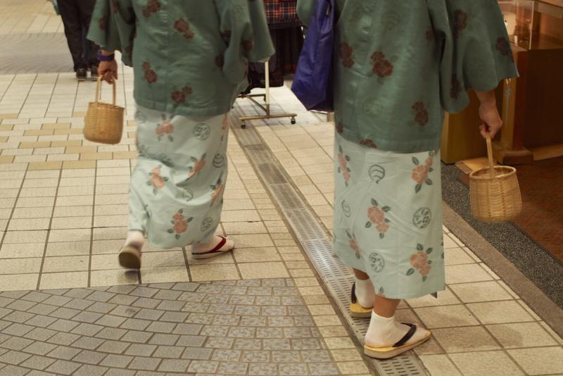 お土産物や飲食店が立ち並ぶ商店街を歩く人の手に、かご。