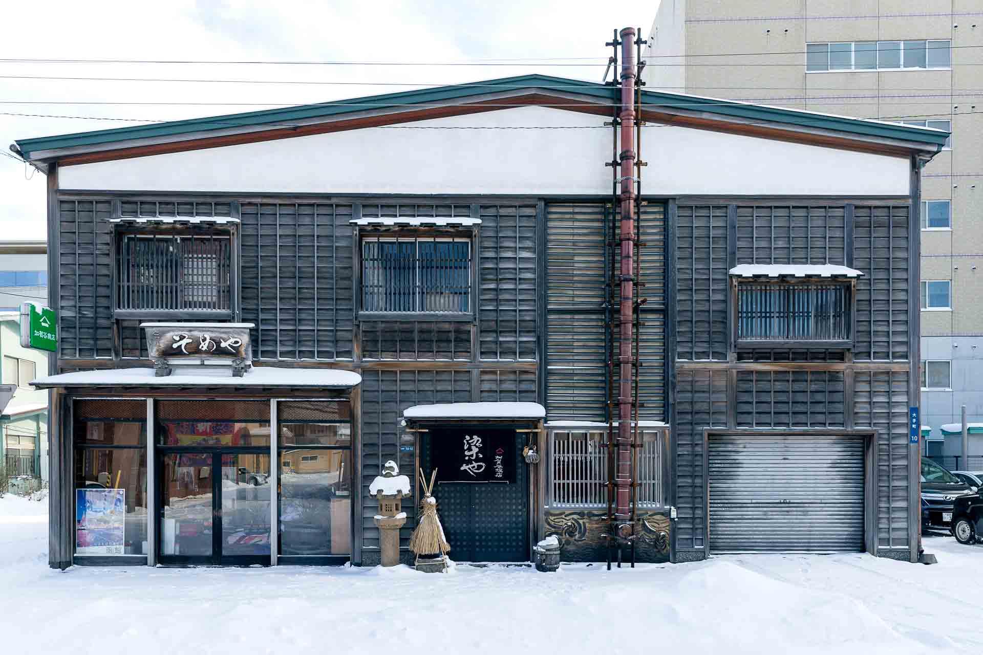 加賀谷旗店の外観。石炭ストーブのための長い煙突が目立ちます