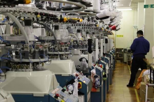 世界的なスポーツブランドの靴下も手がけるキタイさんの製造現場。整然と機械が並ぶ。