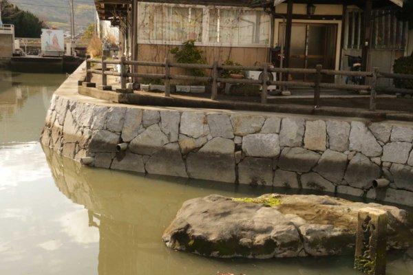 手前の平たい岩が那須与一が矢を放った際に立った場所とされる。用水路の奥に、扇の看板が。
