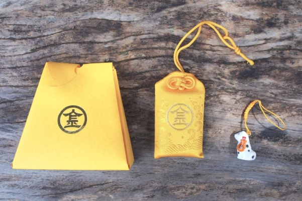「幸せの黄色いお守り」と「ミニこんぴら狗」のセット。こんぴら狗は磁器製でずっしり。