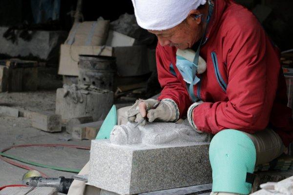 石工団地と呼ばれる石材加工工場の集まる一帯で、石像の加工中の職人さん。