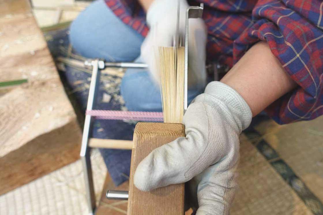 「穂」と呼ばれる、うちわの面の部分の土台を作る工程。「切り込み機」で35〜45本の切り込みを、ものすごい速さで入れていく。印がある訳では無いのに、等間隔で仕上がるのが熟練の技。