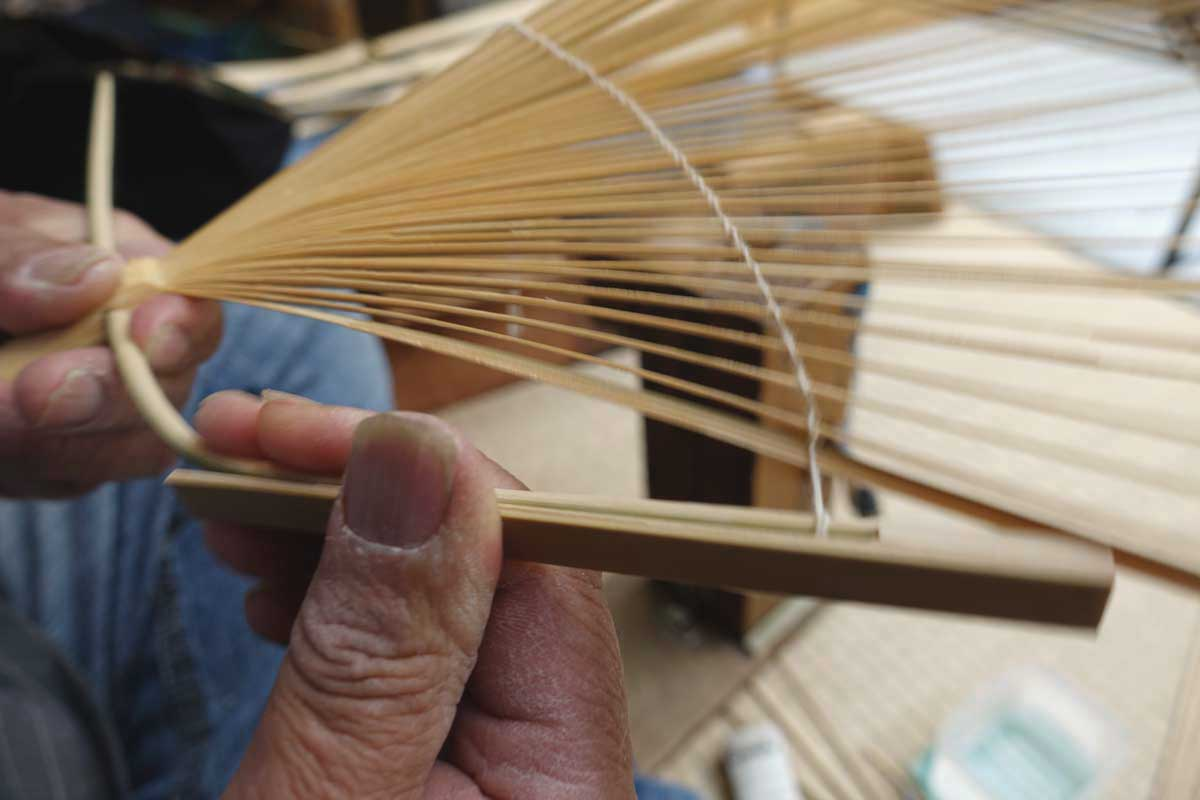 編んだうちわの骨に形を付け、編みを美しく調整していく工程。「付(つけ)」というこの工程は、昔は「付師」がいたほど年季のいる作業なのだそう。