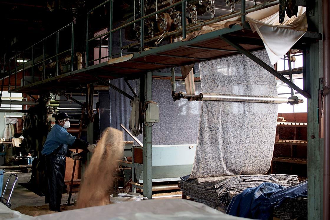 スコップでおがくずを布にかける作業も。広い工場で布がどんどんと変化していきます