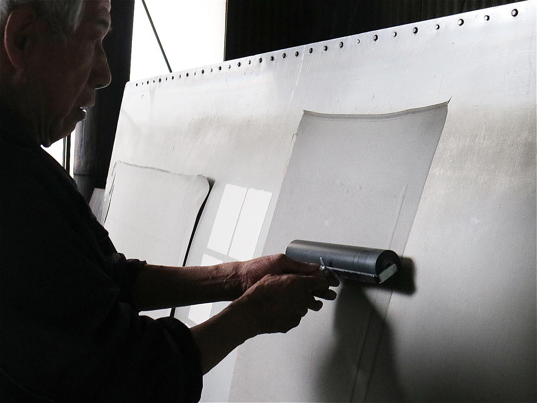 乾燥機の鉄の板に貼り付けて、刷毛とローラーで均一な状態に伸ばします