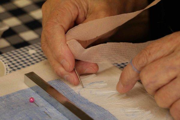 針と手を使って1本ずつ糸を抜いていき、ショールのポイントとなる房を作る