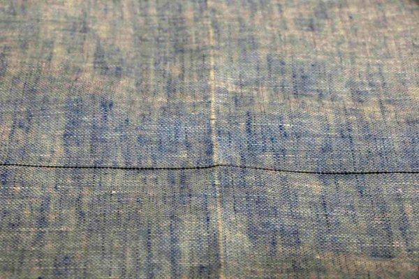 縦の白い筋が糸を抜いた跡。クロスする黒い線は、糸を抜く前。ショールの横幅に合わせてそこだけ違う色糸を織り込み目印にしてある