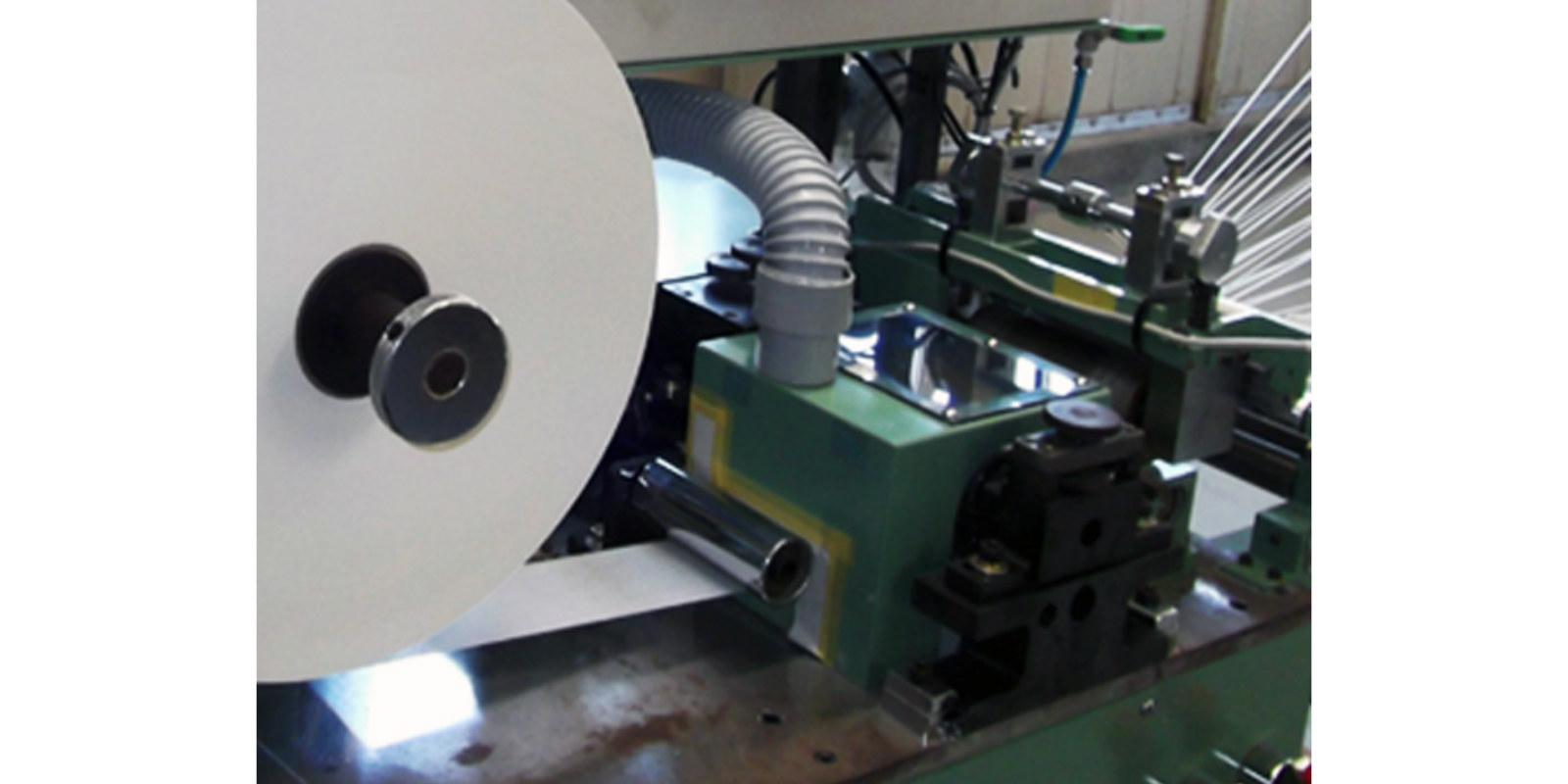 和紙をさらに細く1.5~2ミリ幅にカット。機械の右側から蜘蛛の糸のように裁断後の紙が伸びています