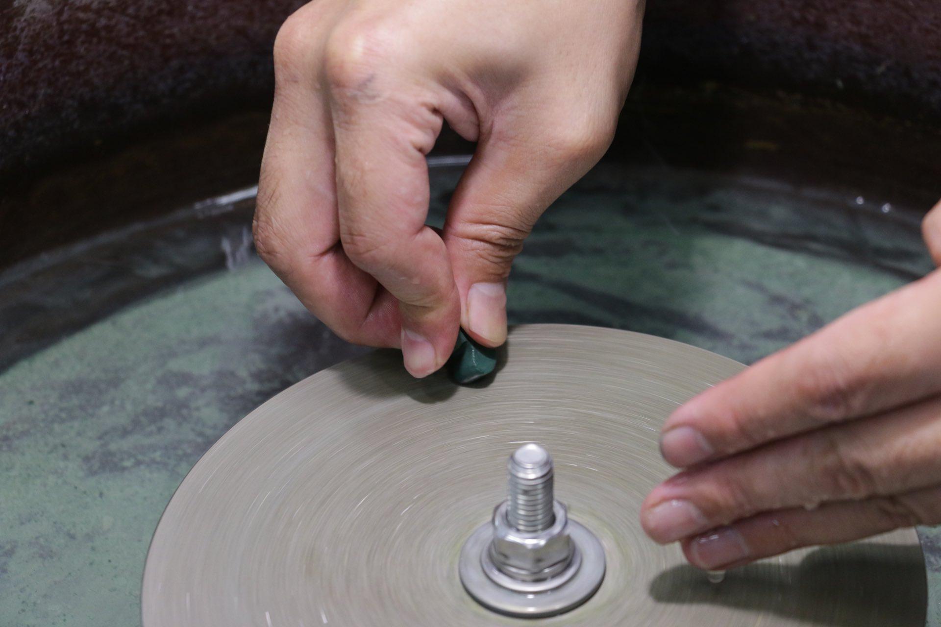 大まかに形を切り出した後は、段階的に道具を変えながら研磨を繰り返します。摩擦熱を抑えるため片手で水を含ませながら、形と表面を整えていきます。