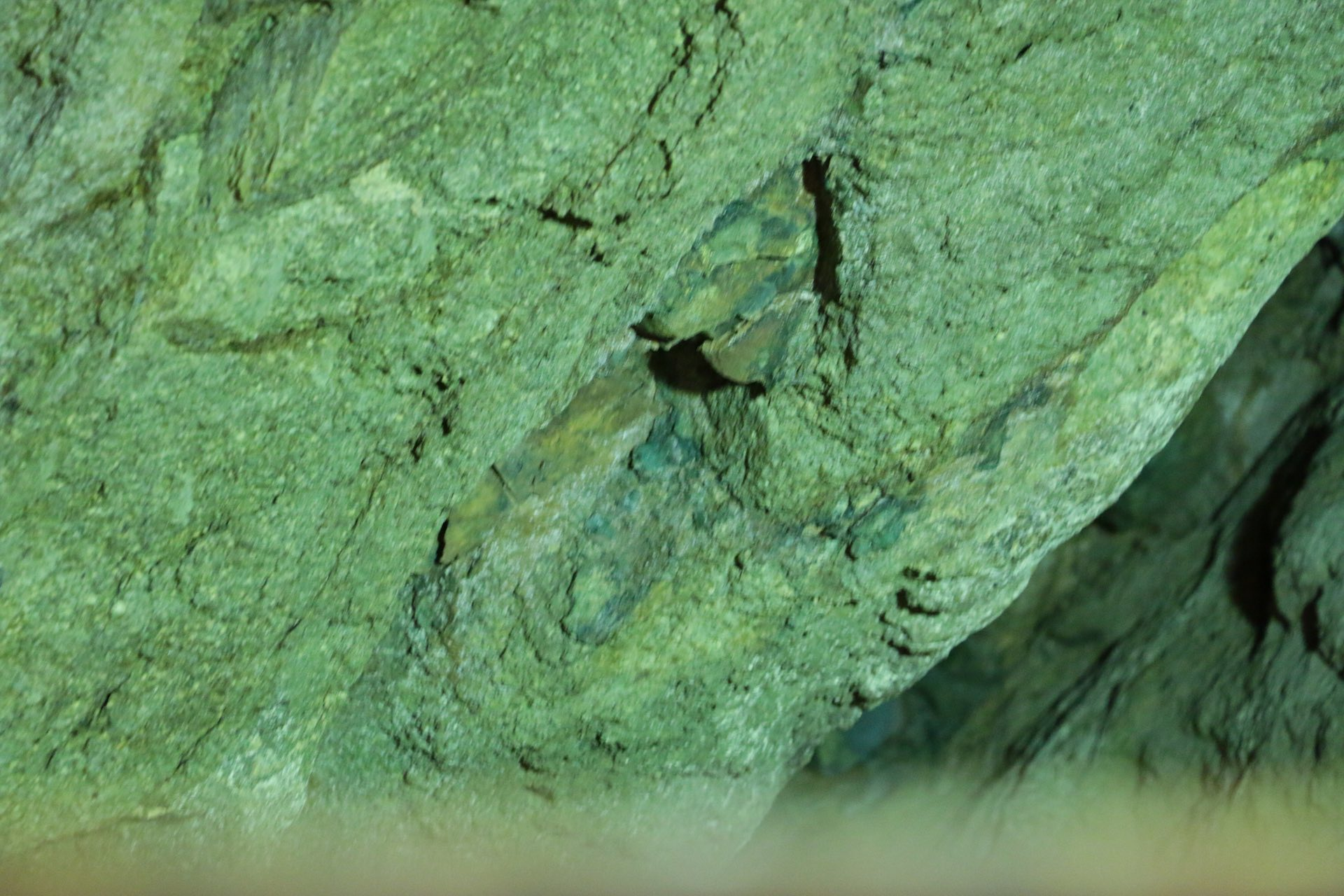 トンネルの奥は、かつての採掘現場の跡。目をこらすと壁に青めのうのような鉱石が