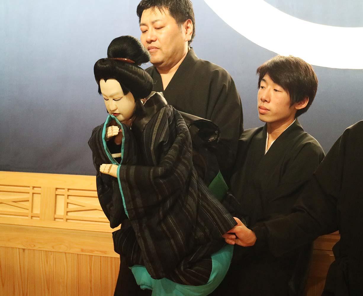 三人で人形を操る様子