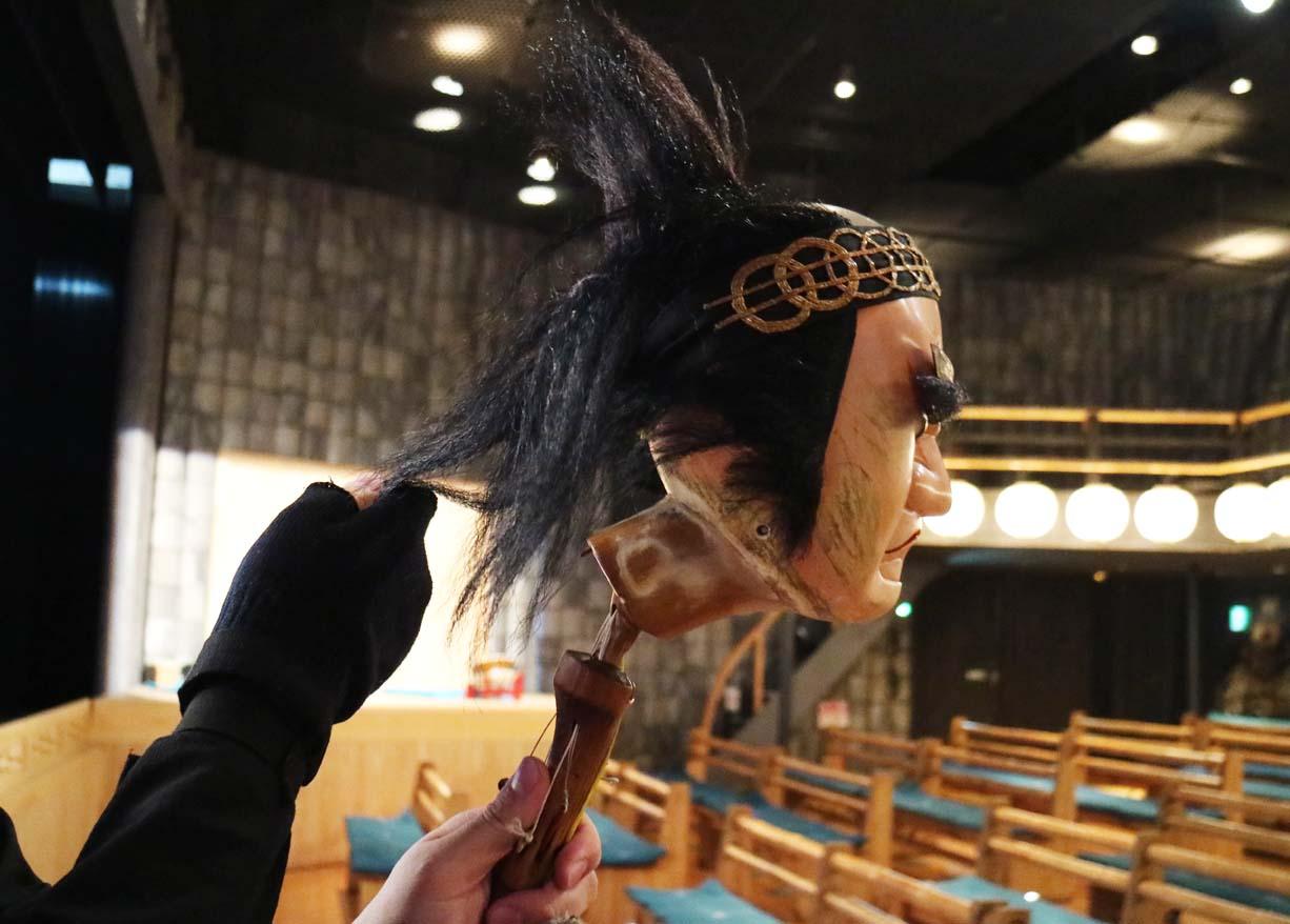 かしらと持ち手は傾いた角度で繋がっていて、人が握った時に人形の顔が正面を向くようになっている。ヘアスタイルなども人形遣いがセットする