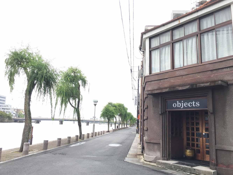 大橋川に掛かる橋を渡り、柳がそよぐ川沿いを少し歩くとお店が現れます