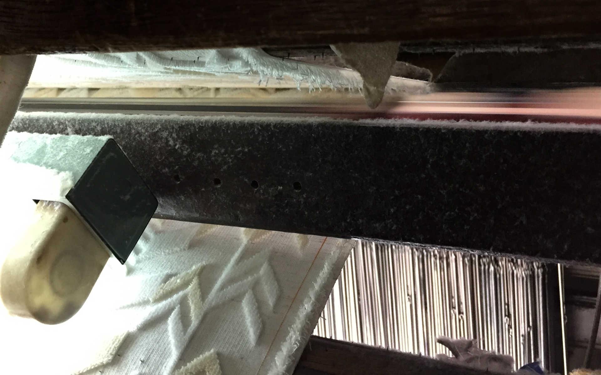 織られた生地は画面上部の刃物で真ん中からカットされていく。すると内側に見事なパイル地が!