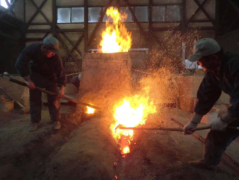 炉の中から不純物の塊「鉄滓」を掻き出しているところ