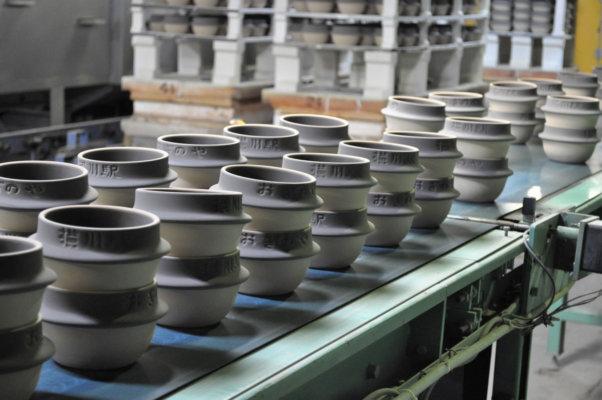 焼成前の土釜がずらり。ベルトコンベアで窯詰め(窯に入れるため、器物を台車に詰める)の工程へ運ばれていく