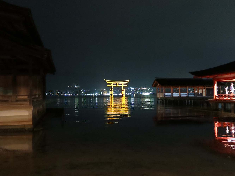 能鑑賞のために海の上に特設された桟敷席からの眺め。嚴島神社の回廊からの眺め。海の向こうには広島の夜景が広がります。大鳥居を隔てて現実世界がはるか遠くに感じられ、神様のいる異界に立ち入っているような気持ちになります