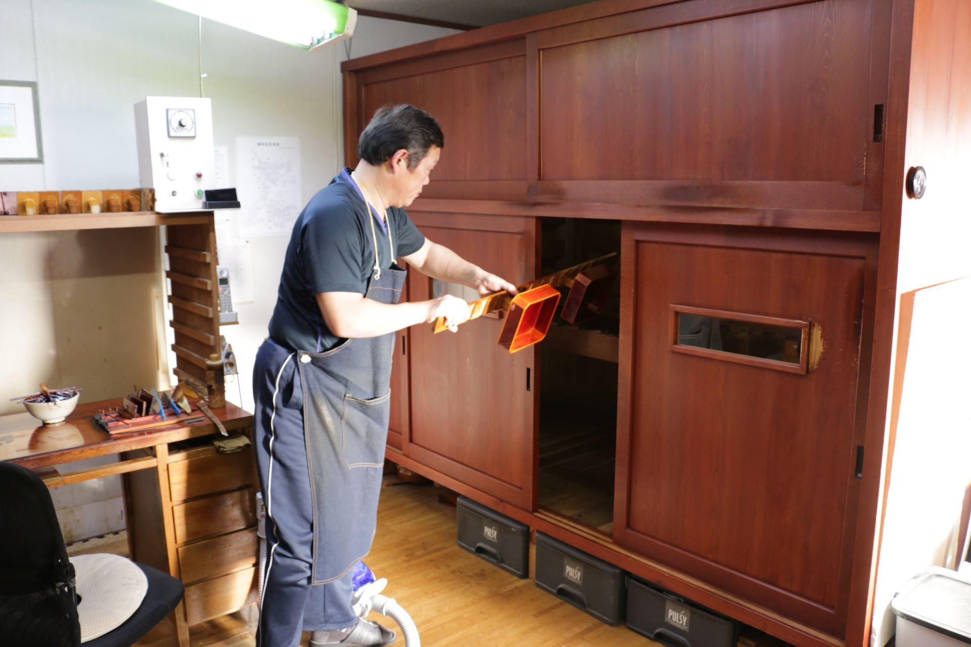 塗り終えた器を漆を乾かす「風炉 (ふろ) 」へ入れているところ