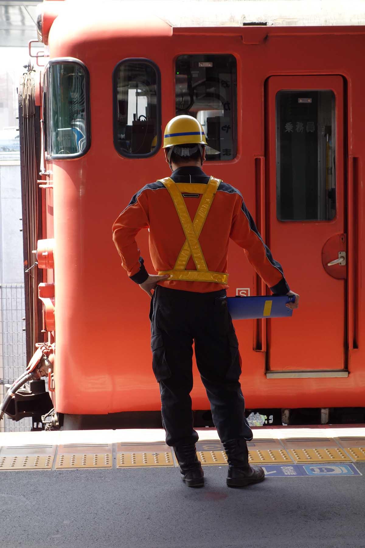 オレンジの電車の前の工事職員の後ろ姿