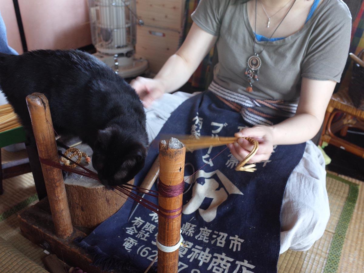きびがら細工を編んでいる丸山さんにじゃれる黒猫