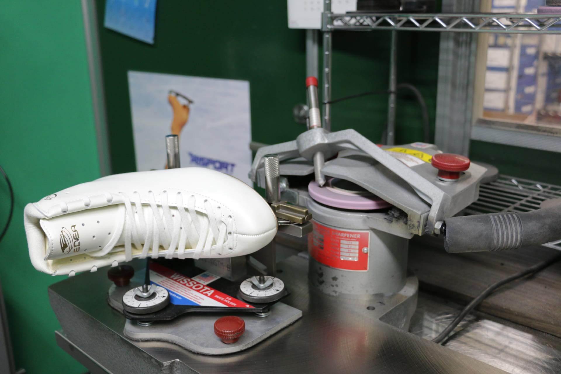 これが研ぎの機械。中央の小さなピンクの円盤がグラインダー (円形の砥石盤) です