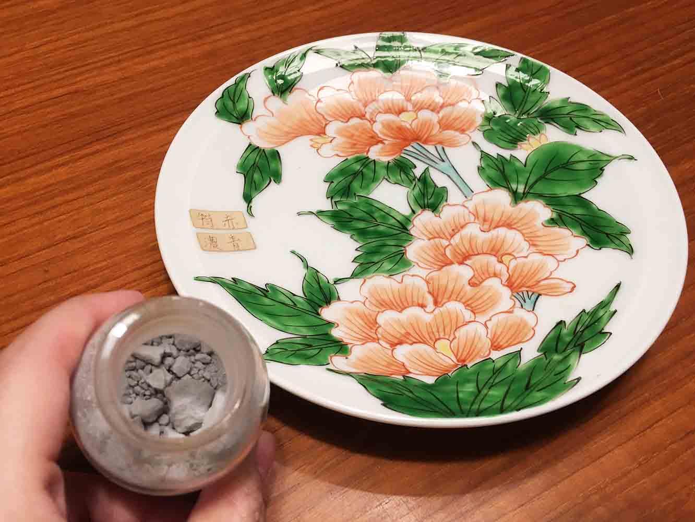 瓶の中のグレー味のある絵具が焼きあがると、皿の上の緑色となる。 (色名は「濃青」)