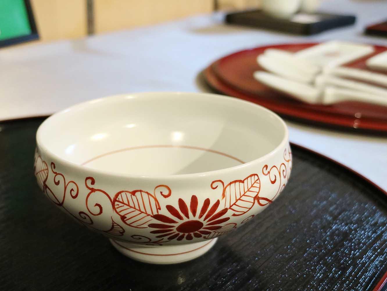 花赤の美しい色が白生地に映える器。店内には、清水焼の職人であった辻氏の作品も並ぶ