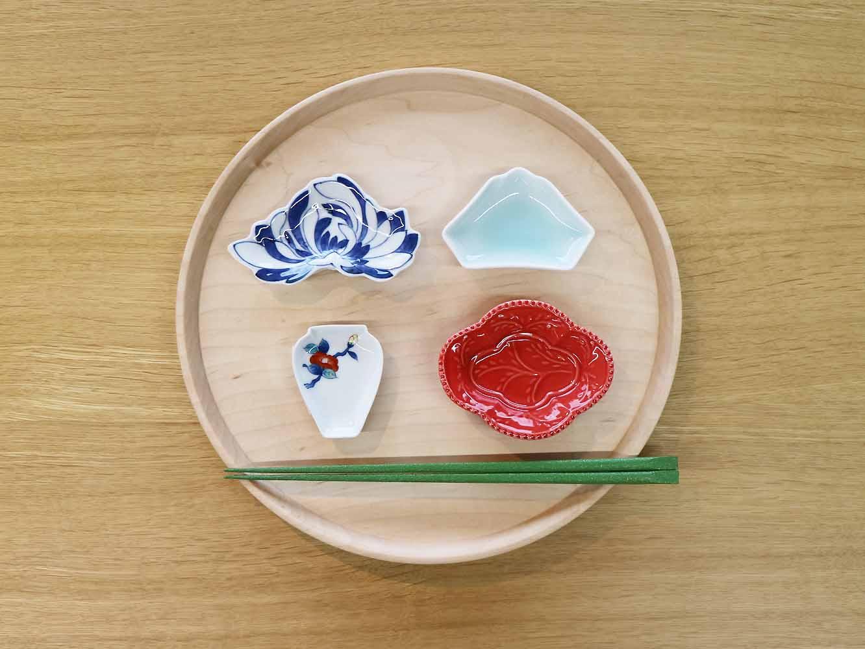 様々なフォルム、絵付けがされた可愛らしいおてしょ皿。お箸と並べるとその小ささがよくわかります