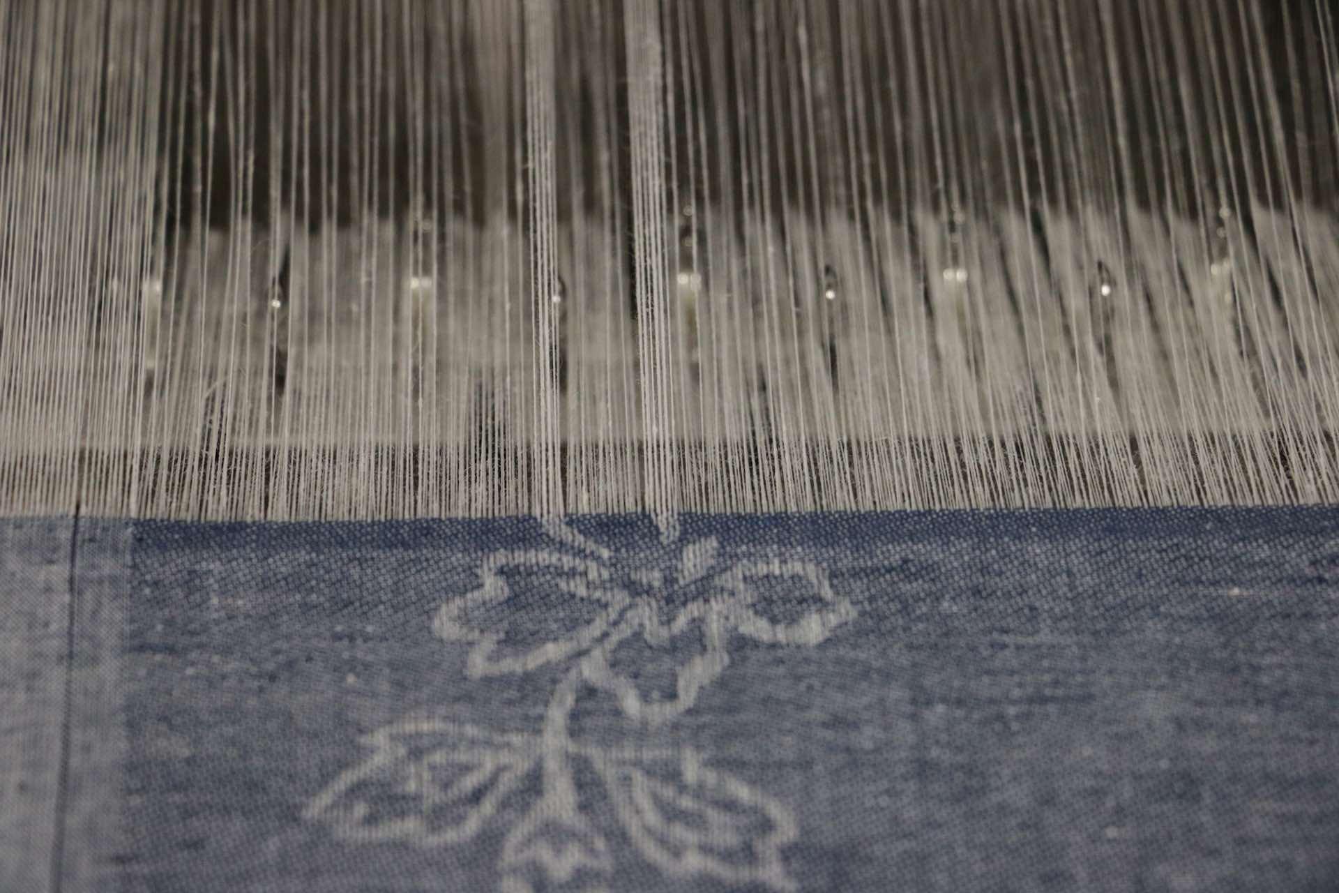 織り途中の様子。模様の部分は、白のタテ糸が多く集まって糸筋がくっきりと見て取れます
