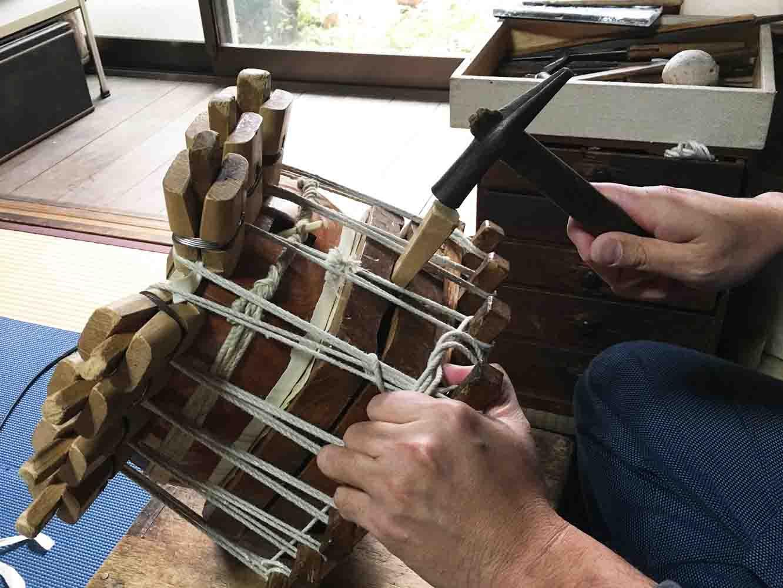 紐をかけ終わったら、道具の隙間に杭を打ち、ジャッキの要領で、さらに皮を張っていきます