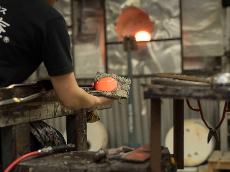 窯で1100度以上の熱で熱して溶けたガラスを成形していく。手で添えているのは濡れた新聞紙
