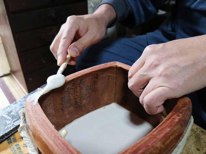 水と練り合わせた糊を三味線の縁に乗せ、その上から皮を貼っていきます。乾燥すると高い粘着性を発揮する糊は、再び水で濡らすと簡単に剥がせるので、貼り替えのたびに楽器を傷つけずにすむのだそう