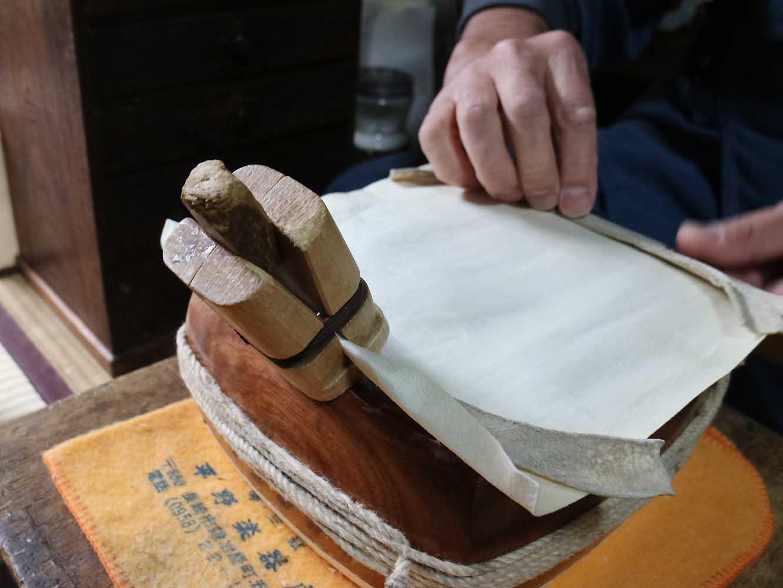 木のクリップのような道具で縁に乗せた皮を仮止めします