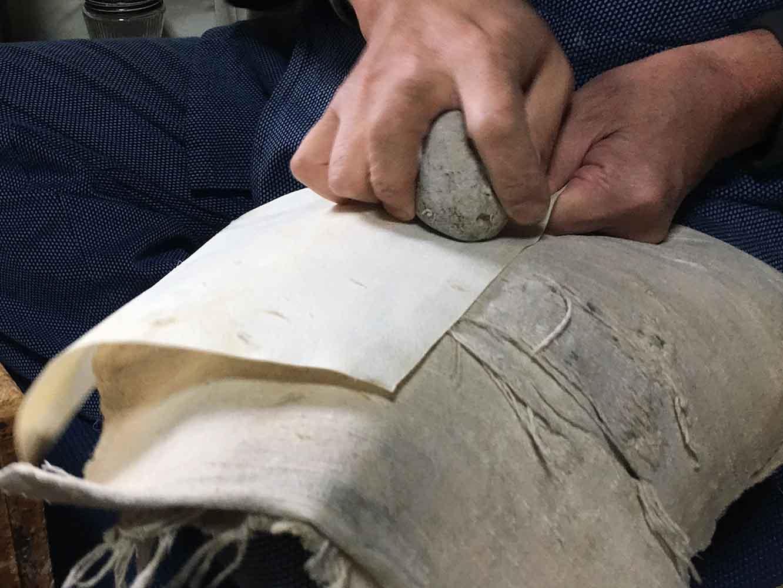 三味線に貼る皮を軽石でこすり、全体の厚みを揃え、表面をなめらかにします