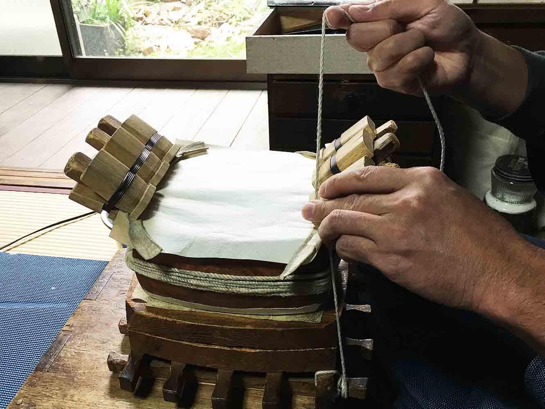 ここで、先ほどの道具が登場します。道具の上に、作業中の三味線の胴を乗せて、紐を掛けます