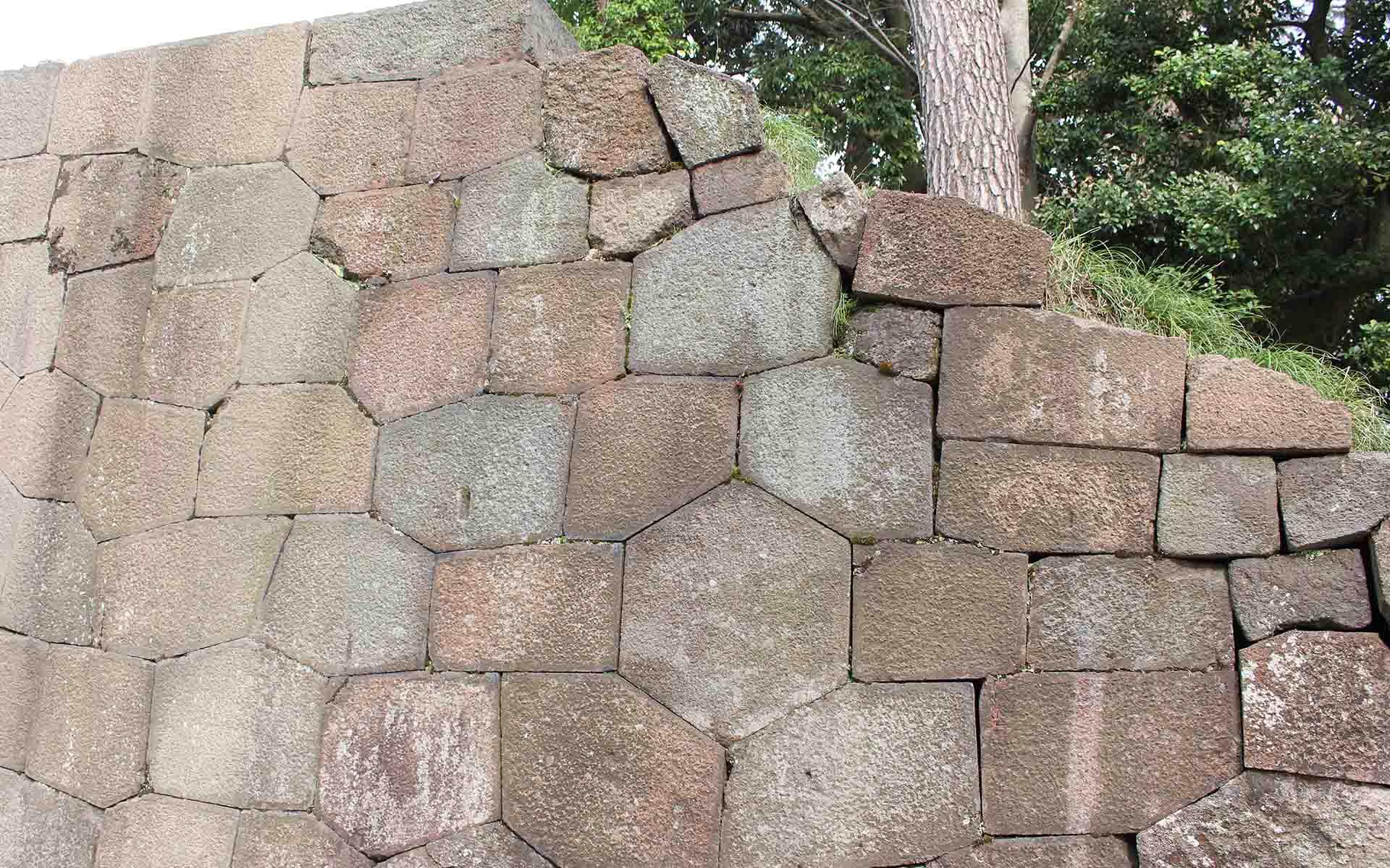 彦三郎さんが手がけた石垣。大火から建物を守った亀甲石(六角形の石)を入組み込むなど、陰陽五行思想の影響もみられる。玉泉院丸庭園の「色紙短冊積石垣」も彦三郎さんが命名
