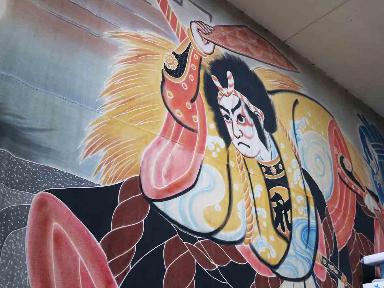 壁一面を覆う巨大な旗。お祭りのために描いたこの図柄は評判を呼び、高知で撮影された緒形拳さん主演の映画「櫂」でも使われたのだそう