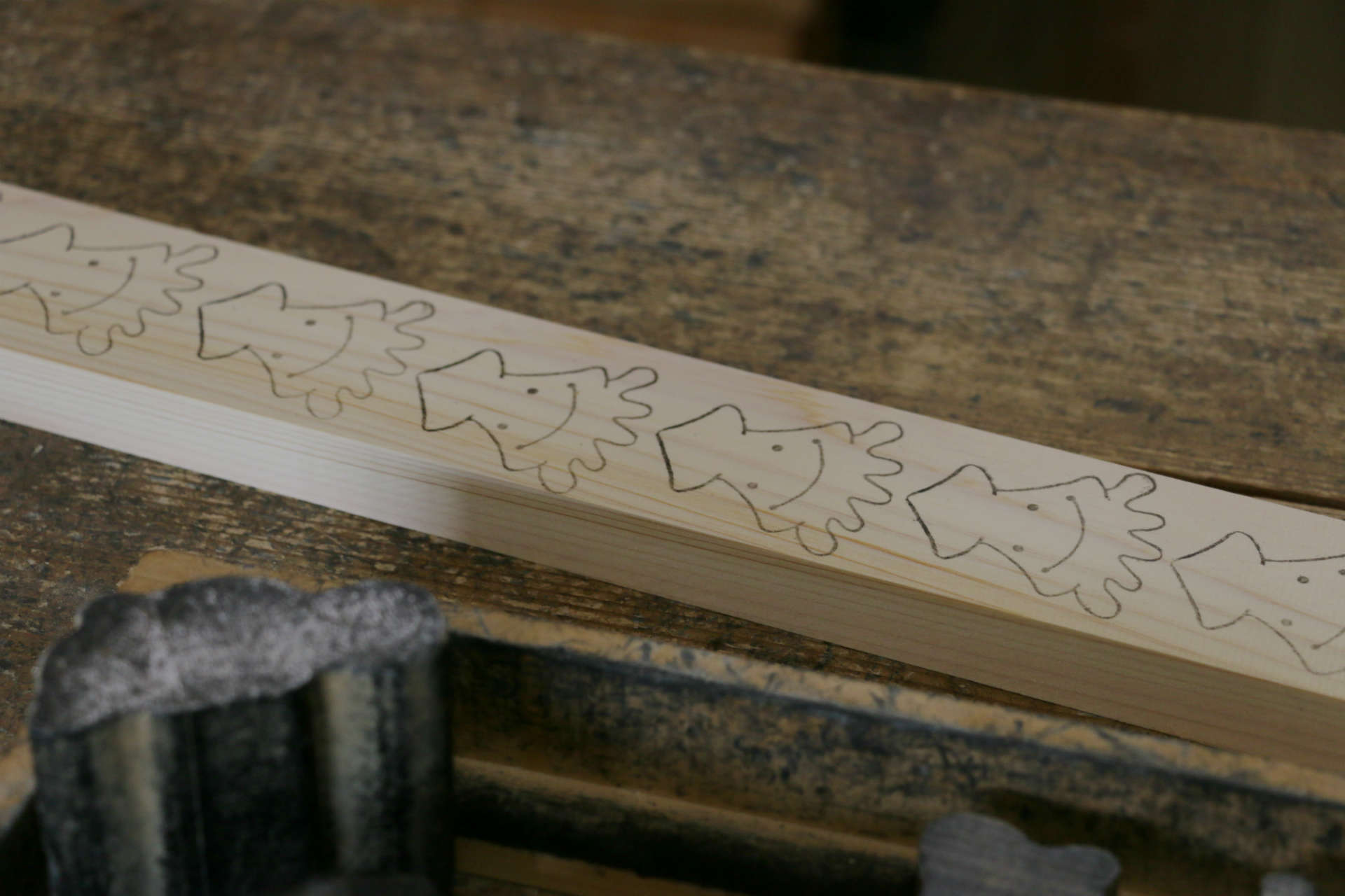 絵付けされた木材。この線に沿って次の工程のスタッフが丁寧に糸のこで切り抜いています