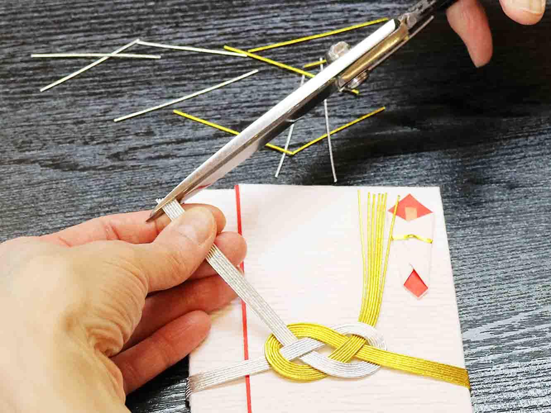 左の指で水引の先端を平らに並べてハサミでカットします。水引に対して直角に切るのがポイント。斜めに切ってしまうと、水引に巻かれている色糸が解けてしまうので注意しましょう