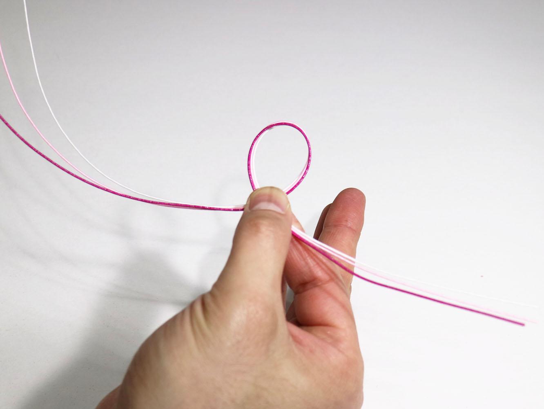 右手で水引の真ん中あたりを持ち、輪っかを作り、親指で押さえます