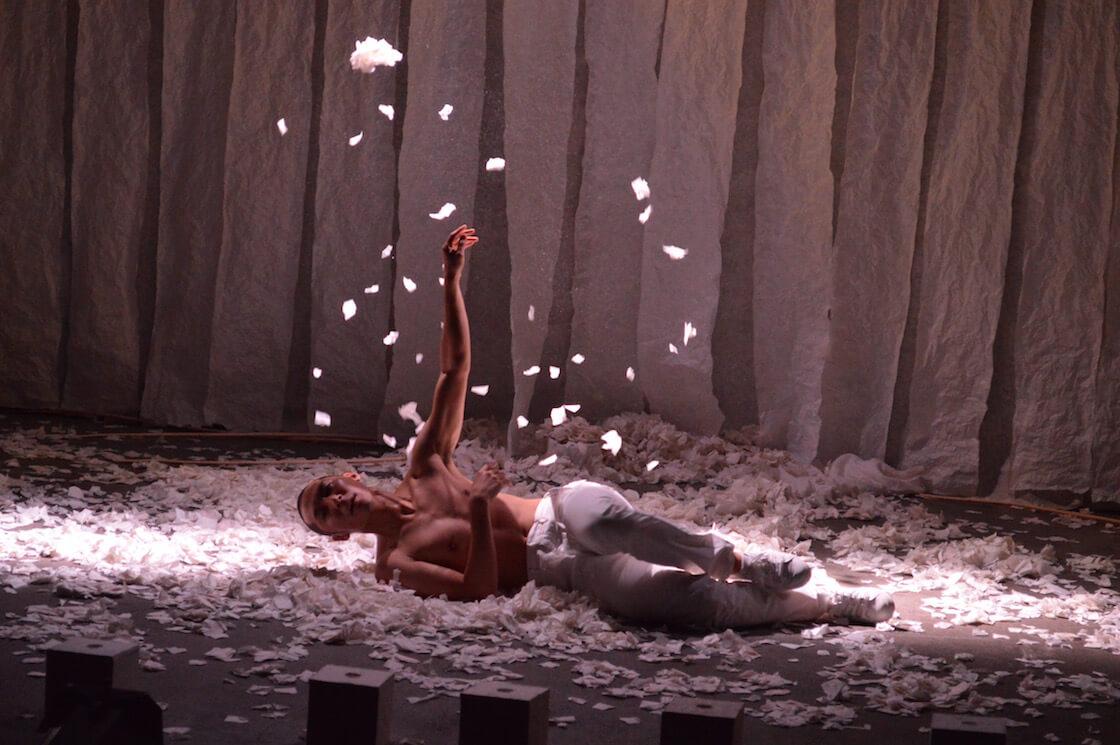 和紙を散らしながら舞うダンサー